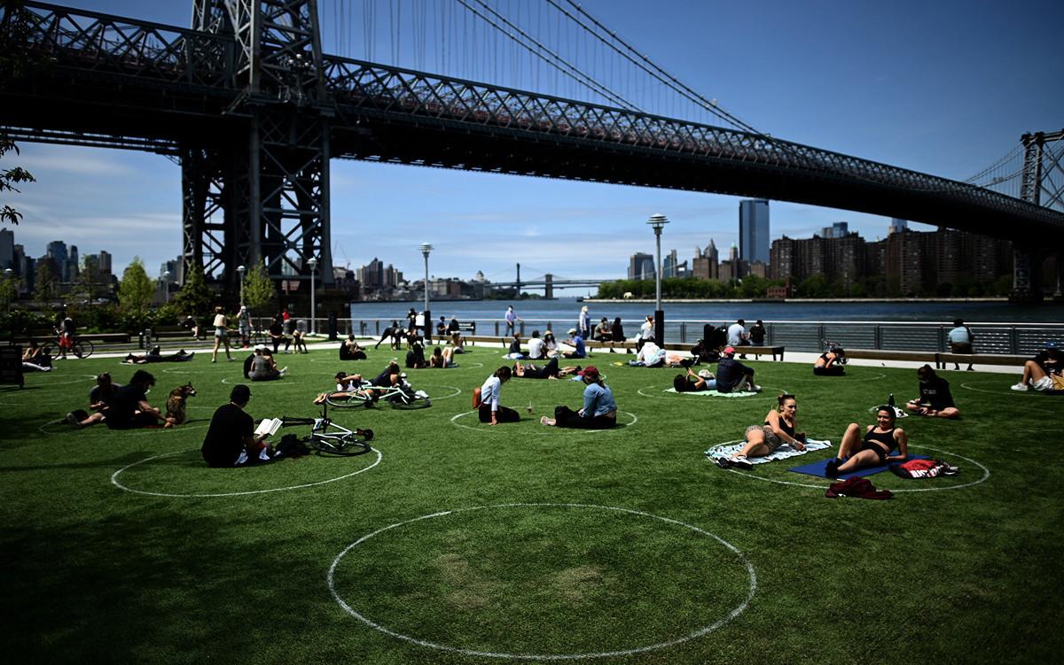 在紐約市布魯克林多米諾公園草坪上,塗了很多白色圓圈,以幫助日光浴者和野餐者保持距離。(Johannes EISELE/AFP)