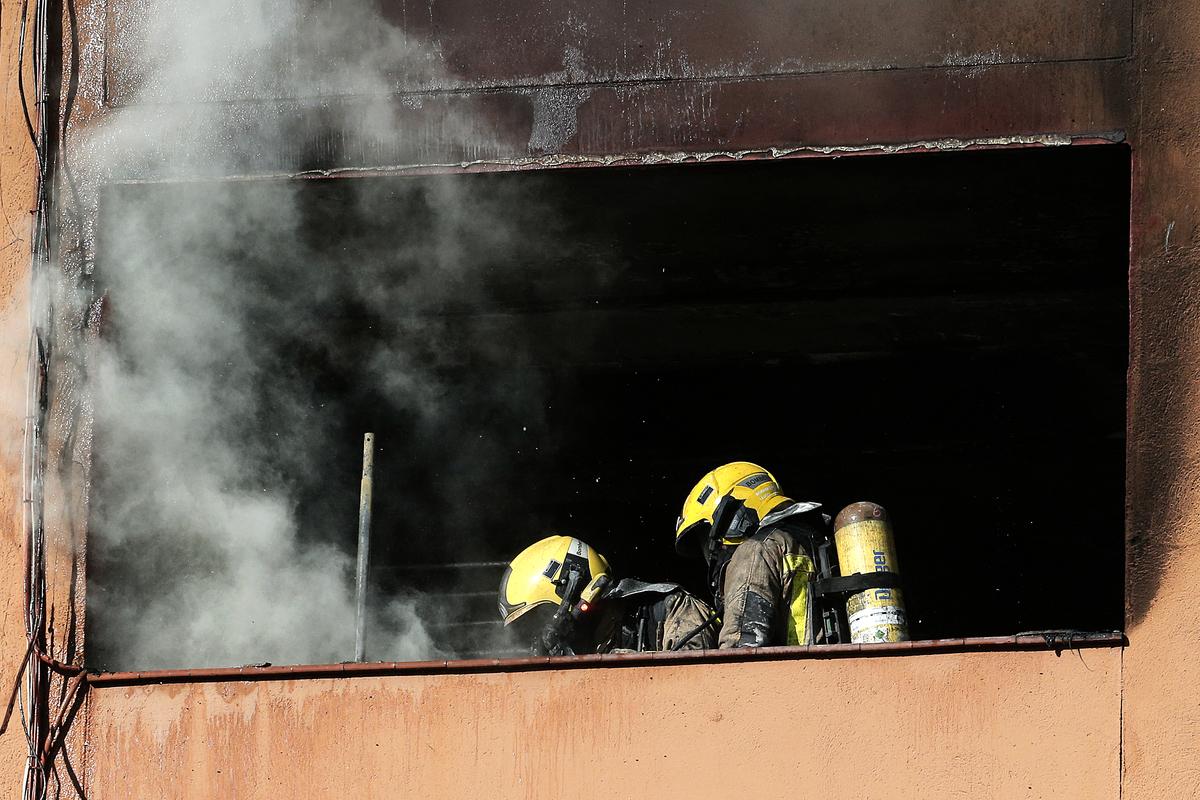 俄羅斯新西伯利亞一棟公寓日前發生火災,一名年輕女子在三樓將兩個年幼的兒子扔下,被鄰居以毯子接住。圖為2019年1月5日,西班牙巴塞隆納附近一棟公寓失火,消防人員正在滅火。(Pau Barrena/AFP)