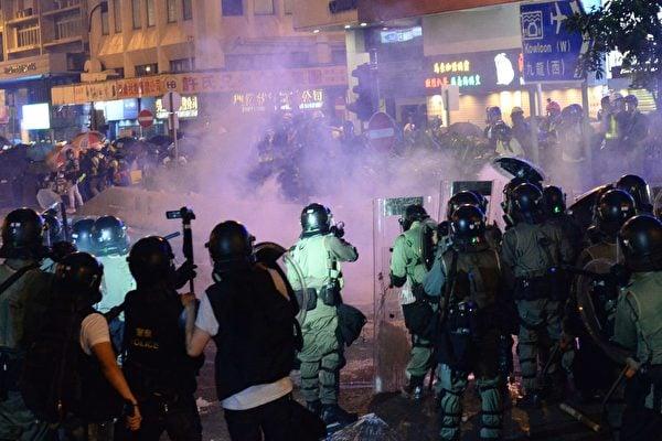2019年7月28日,面對香港警察頻繁發射橡膠子彈及催淚彈清場,許多香港民眾戴上口罩與頭盔,並以雨傘抵抗。(宋碧龍/大紀元)
