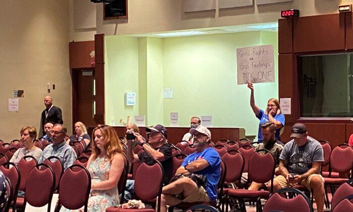 2021年8月11日,在維珍尼亞州勞登郡(Loudoun County)公立學校董事會會議上,當董事會成員傑夫‧莫爾斯(Jeff Morse)發言時,一位女士舉牌抗議。(Terri Wu/The Epoch Times)