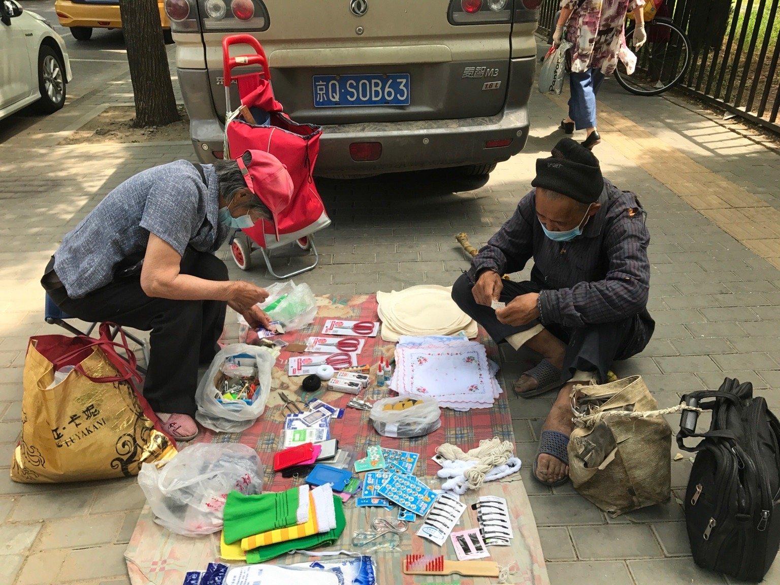2020年6月27日,北京一位已82歲的老人,每月偷偷擺攤,也就掙500元,對面的這位老人是在北京南站的長期上訪人員,他的破包壞了,買了2根線繩給捆上了。(大紀元)
