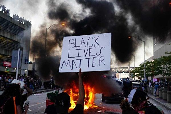 2020年5月29日,在美國佐治亞州亞特蘭大市的一次抗議活動中,一名男子手持「黑人命也是命」的標語牌,旁邊一輛警車在燃燒。(Elijah Nouvelage/Getty Images)