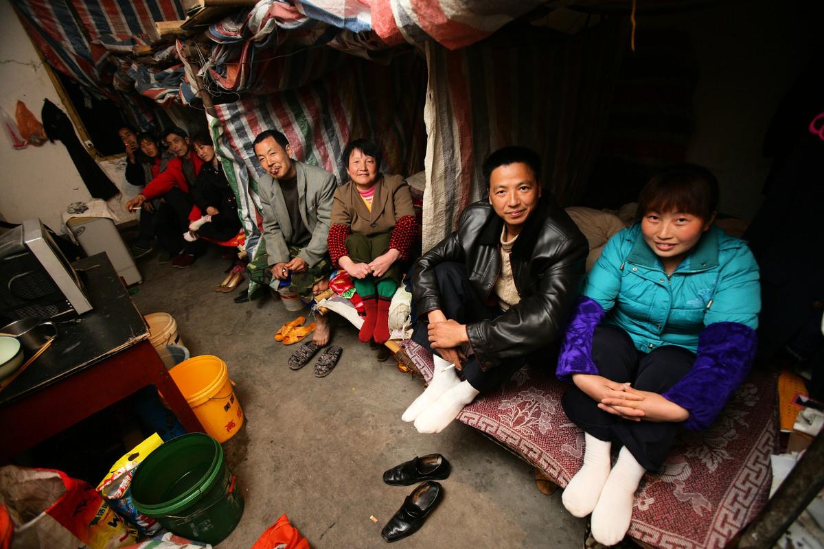 農民工的生活條件都比較差,在新疆還要住土房、搭帳篷。圖為示意圖,四對重慶民工夫婦在塑料布做成的風雨棚裏。(China Photos/Getty Images)
