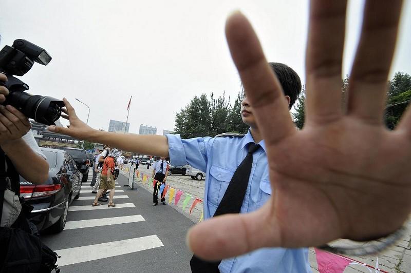 駐華外國記者協會發佈報告說,中共政府正以「史無前例」的力度,把簽證當作武器,威脅外國媒體。圖為一名警察正用手阻擋記者的拍照。(JEWEL SAMAD/AFP/Getty Images)