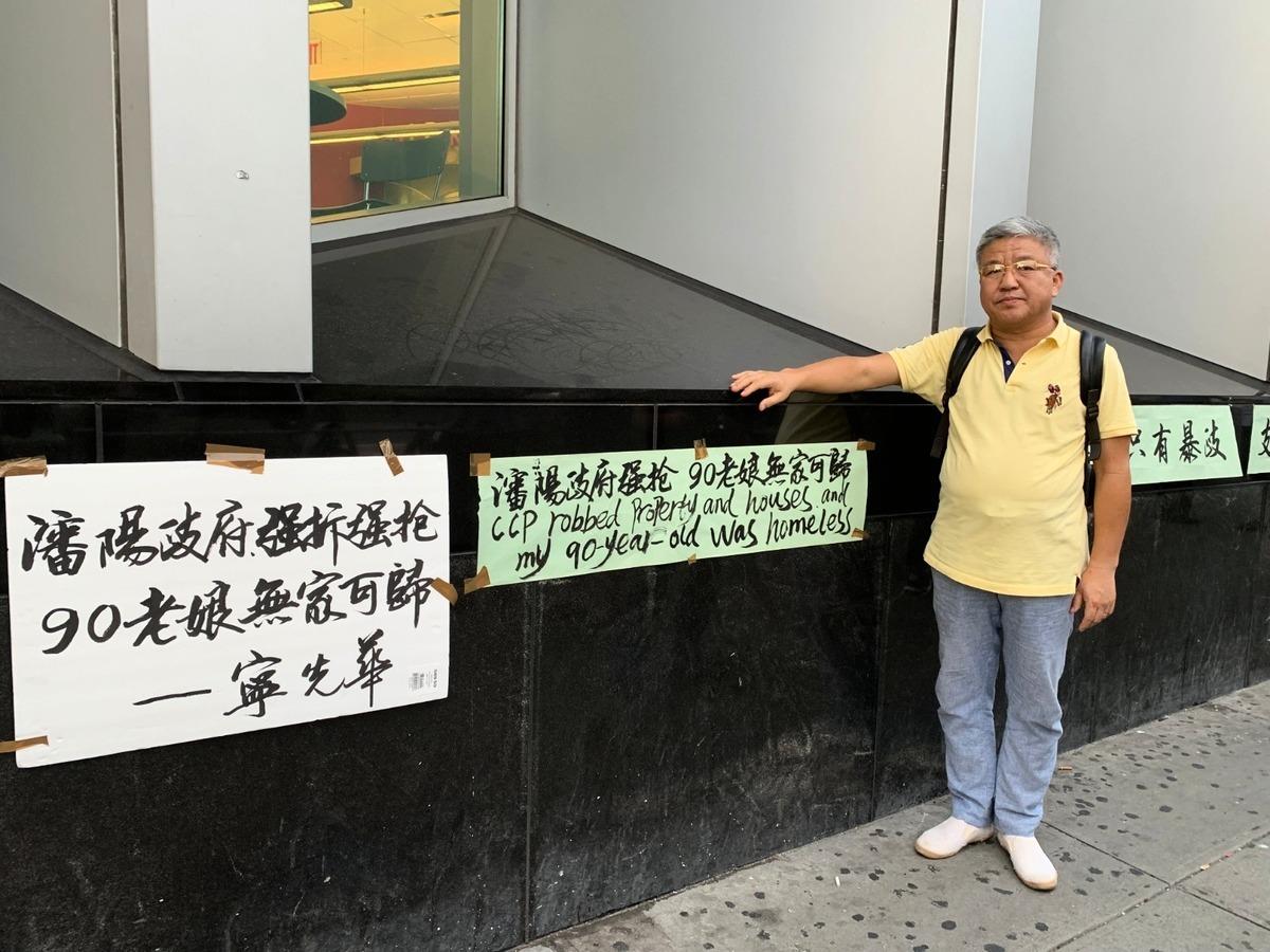 寧先華在法拉盛圖書館前舉牌控訴中共瀋陽政府強拆民宅,導致他九十多歲的母親無家可歸。(林丹/大紀元)