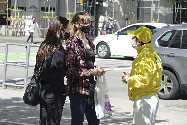 2021年5月2日,溫哥華部份法輪功學員在市中心的藝術館前煉功,慶祝法輪大法日,一些人主動來了解。(大宇/大紀元)