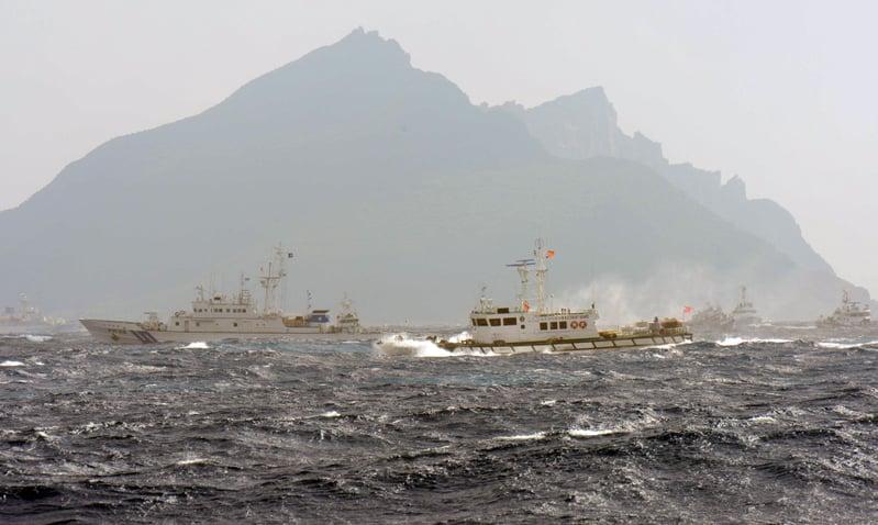 中共海警船3月29日進入釣魚台海域,日本發出持續警告。本圖後方的小礁島即為釣魚台,左邊的船艦是日本海上保安廳的巡邏艦。(攝影YEH/AFP/GettyImages)