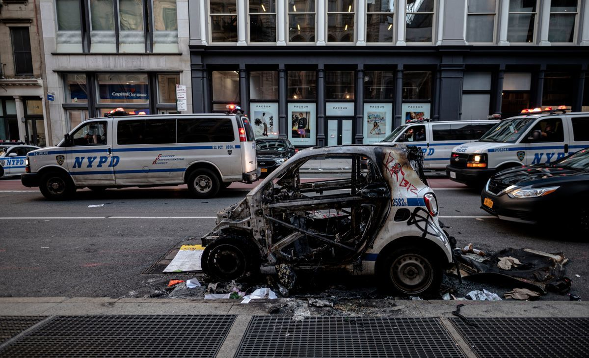 圖為2020年6月1日在紐約市曼哈頓舉行的抗議喬治・弗洛伊德(George Floyd)身亡的活動中,有警車被燒燬,還有遊行街道周邊的商店被砸。(JOHANNES EISELE/AFP via Getty Images)