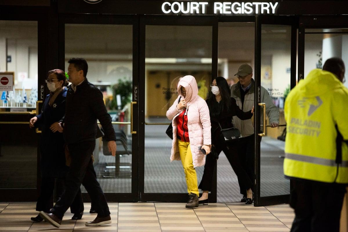 2018年12月11日,在加拿大卑詩省高等法院對華為首席財務官孟晚舟的保釋聽證會後,一群戴口罩、不想讓媒體拍到臉部的華人離開法院登記處。(Jason Redmond/AFP/Getty Images)