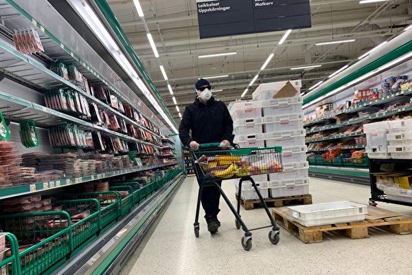 3月底,中共病毒(武漢肺炎)疫情在芬蘭爆發。圖為3月28日,一名男子戴著扣罩在芬蘭瓦薩(Vaasa)的一家超市購物。(OLIVIER MORIN/AFP via Getty Images)