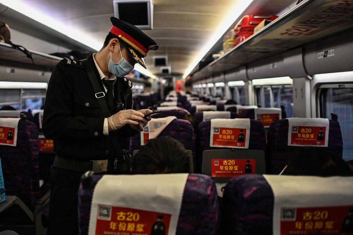 列正在離開上海的火車上,有檢查人員戴著口罩和手套,驗證旅客手機信息。(Hector Retamal/AFP via Getty Images)