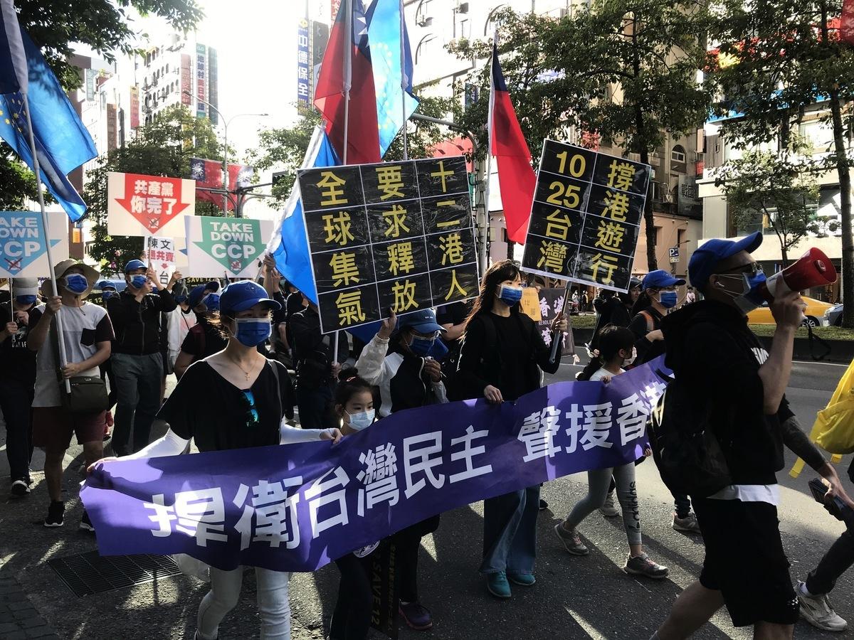 台灣多個公民團體2020年10月25日在台北舉行「台灣撐港遊行」,參與民眾穿黑衣、舉黃傘及標語,訴求為要求中共和港府立即釋放12位港人。(李怡欣/大紀元)