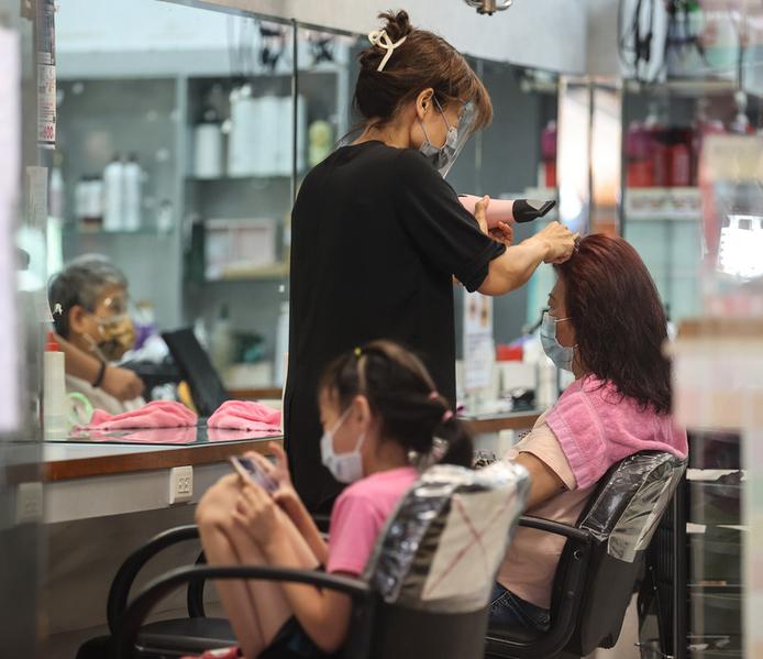 台灣第三級警戒延到7月26日,但適度鬆綁,有民眾21日前往髮廊理髮,店內全體人員都戴好口罩。(中央社)