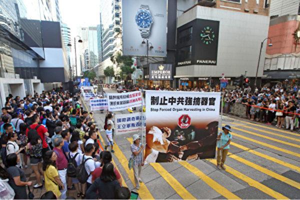 法輪功學員制止強摘器官大遊行途經香港尖沙咀廣東道鬧市,吸引市民遊客駐足觀看。(潘在殊/大紀元)