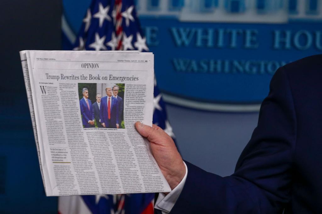 2020年4月19日美國總統特朗普在每日疫情簡報會上,手拿一份美國報紙。(asos Katopodis/Getty Images)