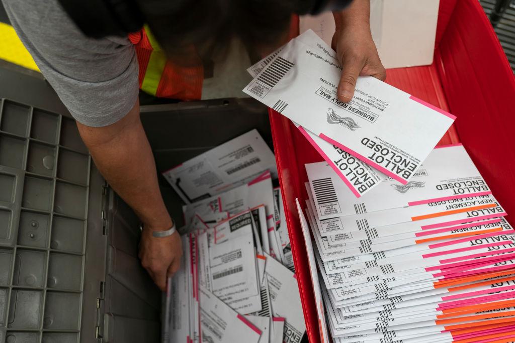 2020年11月2日,在俄勒岡州波特蘭市的姆爾特諾默縣(Multnomah County)選物處,一名工作人員正在整理提交的選票。(Nathan Howard/Getty Images)