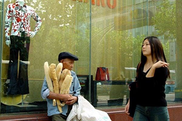大陸的消費市場近來出現了後勁不足的信號。圖為上海淮海路上賣自己農產品的農民與時尚服飾櫥窗。(大紀元資料室)