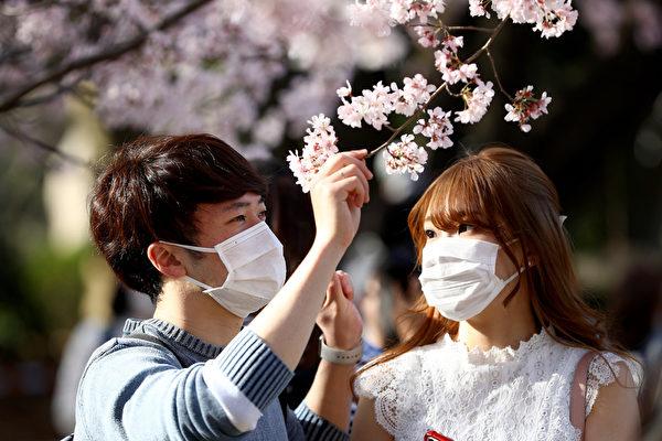 Iris Ohyama公司決定把口罩不織布生產線撤出大陸,回流日本,並從6月份開始增加日本工廠的口罩產量。圖為2020年3月21日,日本戴著口罩的市民在東京上野公園,欣賞盛開的櫻花。(Clive Rose/Getty Images)