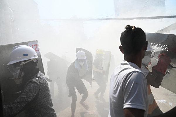 2021年3月8日,仰光民眾在街頭抗議軍事政變時,帶著自製的簡易盾牌來防禦武警發射的催淚彈。(STR/AFP via Getty Images)