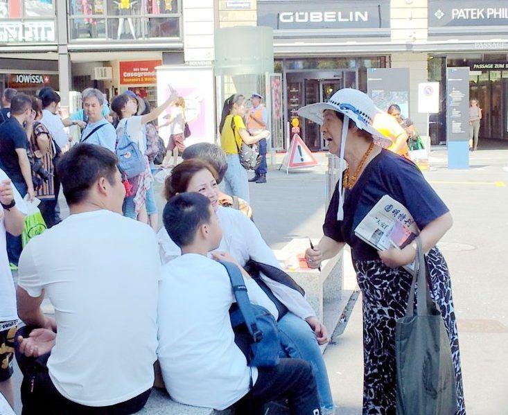2019年6月在盧塞恩景點,79歲的潘淑珍給中國遊客們講真相。(潘淑珍提供)