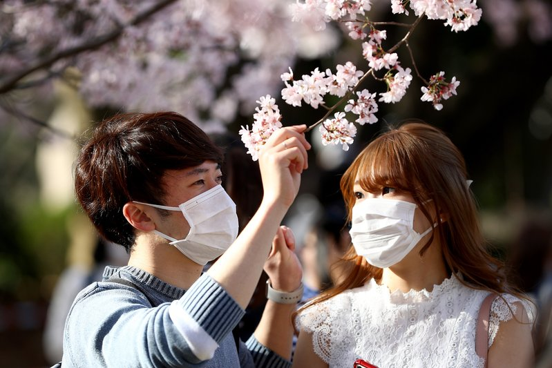 日本政府正著手與400企業合作本土生產醫療戰略物資。圖為2020年3月21日,日本戴著口罩的市民在東京上野公園,欣賞盛開的櫻花。(Clive Rose/Getty Images)