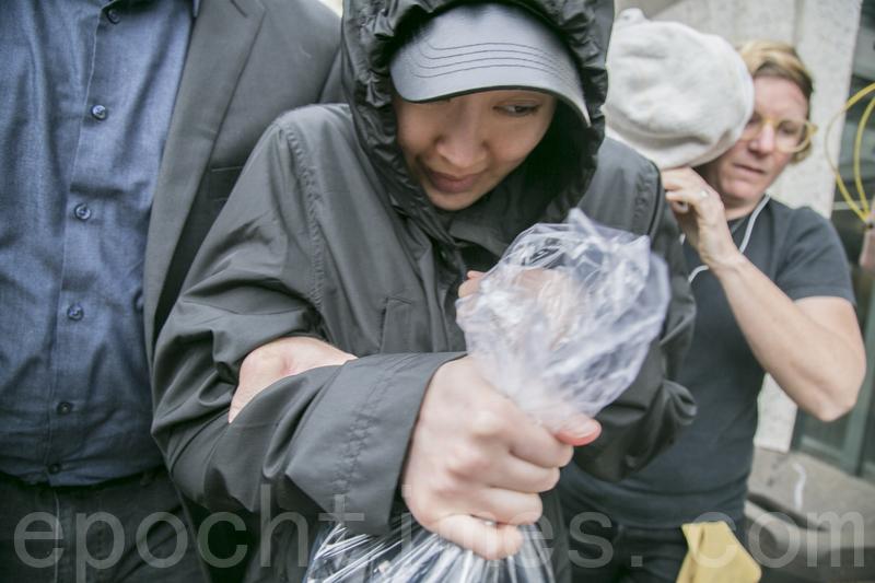 圖為2017年4月6日下午2時左右,李凡妮在律師們的簇擁下快速閃避記者,上車離去。(曹景哲/大紀元)