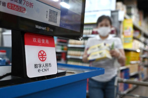 2021年7月2日,在北京一家沃爾瑪商店,一名婦女走近收銀台,那裏有一個標誌牌,上面顯示接受「數碼人民幣」付款。(GREG BAKER/AFP via Getty Images)