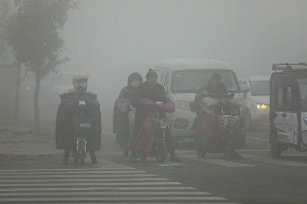 大陸多地遭新年首輪「霾伏」,69個市啟動重污染預警。圖為2019年12月7日,人們在陰霾籠罩的山東菏澤曹縣街頭騎行。(大紀元資料室)
