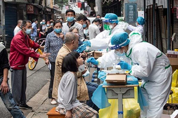 2020年5月15日,在疫情爆發最嚴重的中國湖北省武漢市,身穿防護服的醫務人員在小區內進行核酸檢測。(STR/AFP via Getty Images)