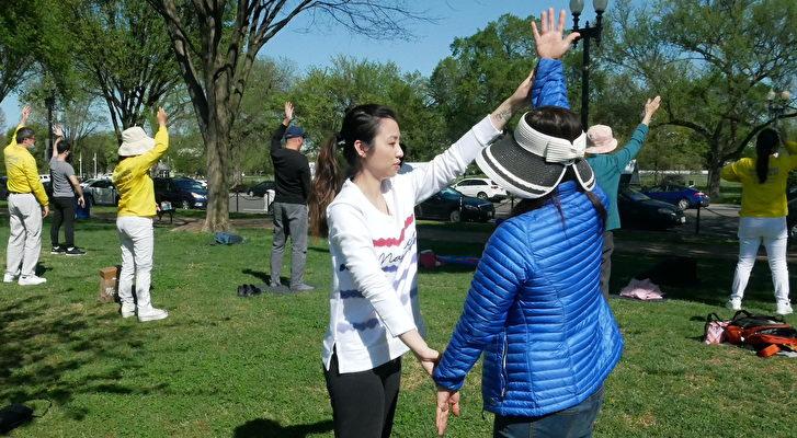 4月11日,新學員(右穿藍色上衣者)在現場學習如何煉功。(董韻/大紀元)