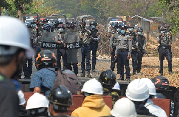 2021年3月8日,在內比都(Naypyidaw)的抗議軍事政變活動中,赤手空拳的抗議者與手持槍支的武警對峙。(STR/AFP via Getty Images)