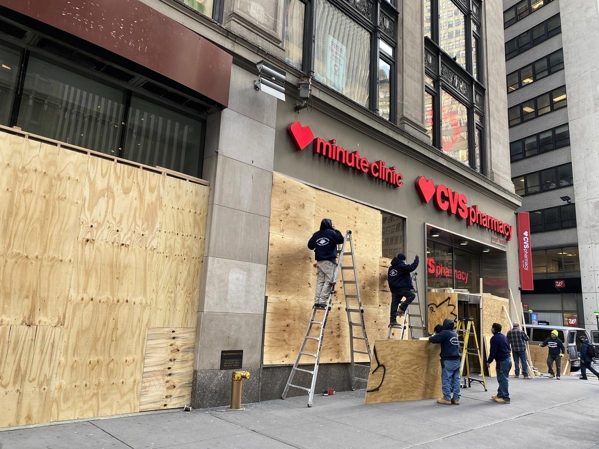 時代廣場附近的CVS藥店正在店外釘上木板。(張本真/大紀元)