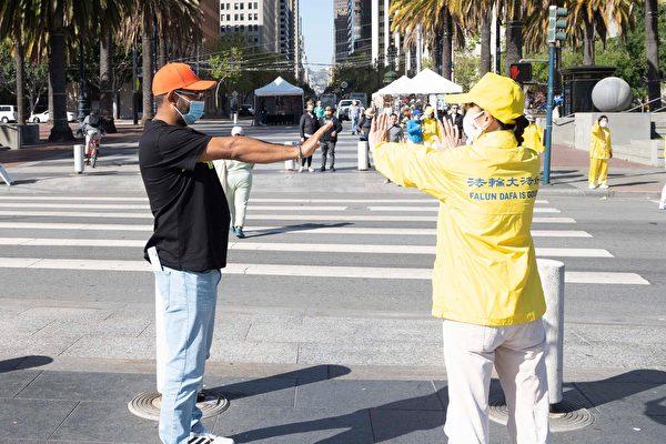 從佛羅里達州來加州旅遊的弗雷德‧瓦勒斯(Fred Valles)(左),在學煉法輪功功法。(周容/大紀元)