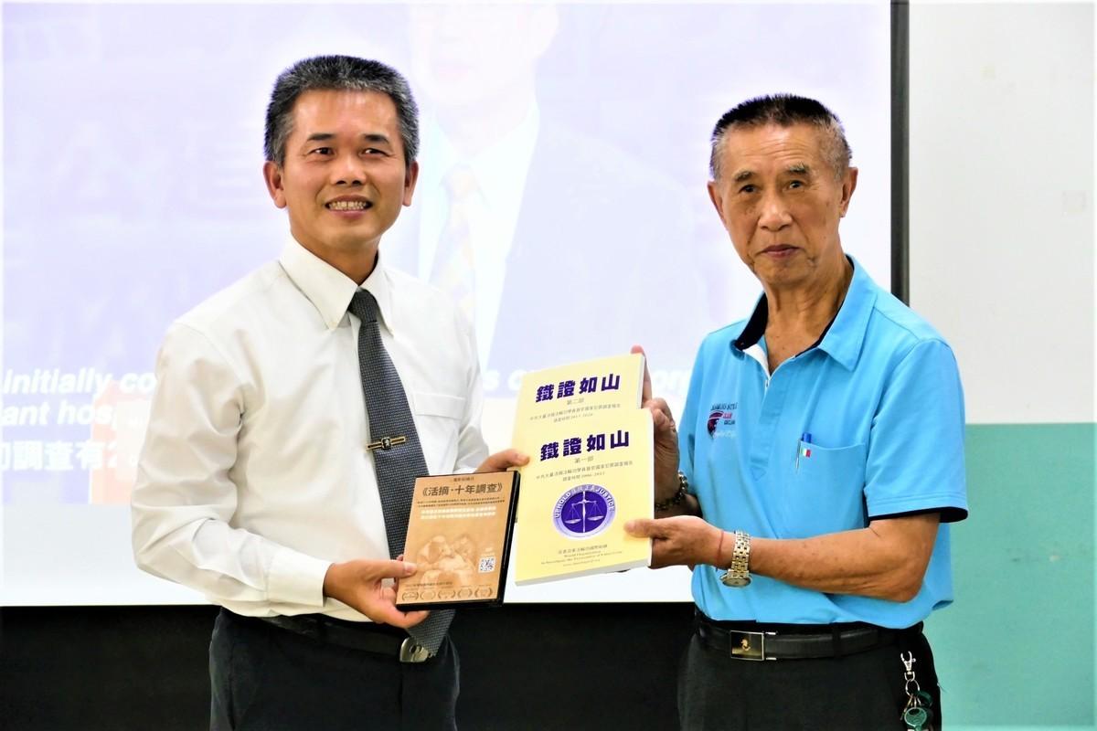 追查組織台灣分會會長、前軍事檢察長李正雄(左)贈送「鐵證如山」給本次支持首映會的樂天宮主任委員葉敏雄(右)。(鄧玫玲/大紀元)