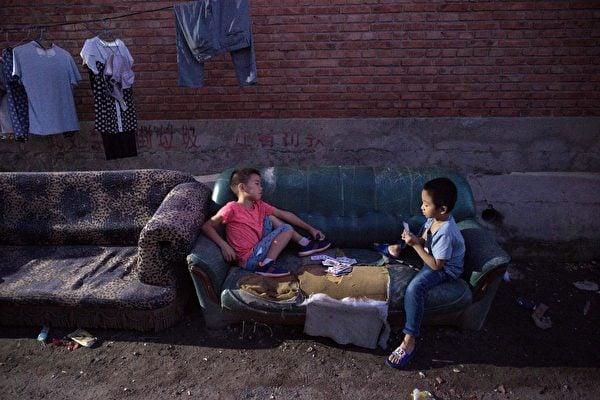 在北京郊區的一個移民村,男孩晚上打牌。攝於2017年9月7日,(Nicolas Asfouri/AFP/Getty Images)