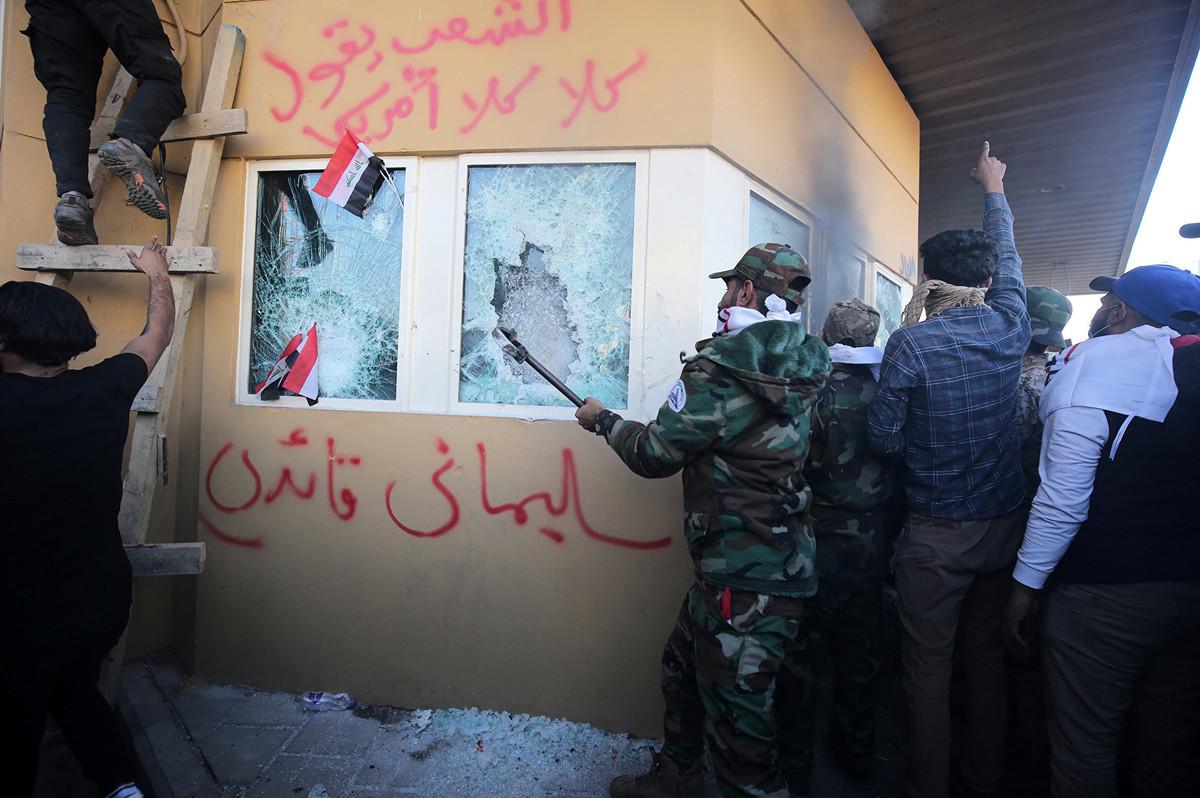 2019年12月31日,親伊朗的伊拉克什葉派民兵組織「真主黨旅」、「正義聯盟」、「人民動員組織」的成員或支持者翻過美國駐伊拉克大使館的外牆、闖入使館進行破壞,並向安保人員投擲石塊和水瓶。(AHMAD AL-RUBAYE/AFP via Getty Images)