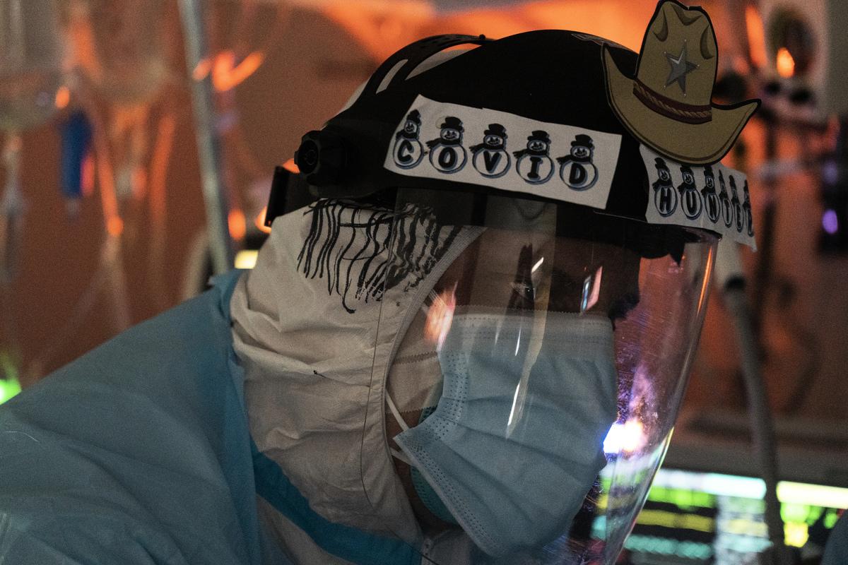 2020年12月22日,位於德薩斯州侯斯頓的美國聯合紀念醫療中心的醫生在對中共病毒(武漢病毒)深切治療部(ICU)患者進行氣管切開術時,觀察內窺鏡屏幕。(Go Nakamura/Getty Images)