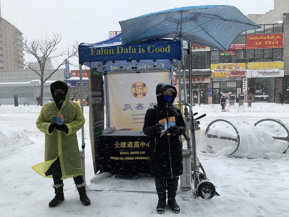 暴風雪襲紐約,當天狂風呼嘯,降雪超過1呎,但法輪功學員如常堅守真相點,向民眾傳遞「法輪大法好」的福音。(林丹/大紀元)