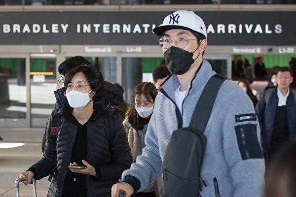 圖為1月29日帶著面罩的旅客抵達洛杉磯國際機場。(MARK RALSTON/AFP via Getty Images)