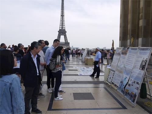 「4.25」和平上訪20周年,法輪功學員在巴黎人權廣場舉辦紀念活動。圖為遊人觀看真相展板。(明慧圖片)
