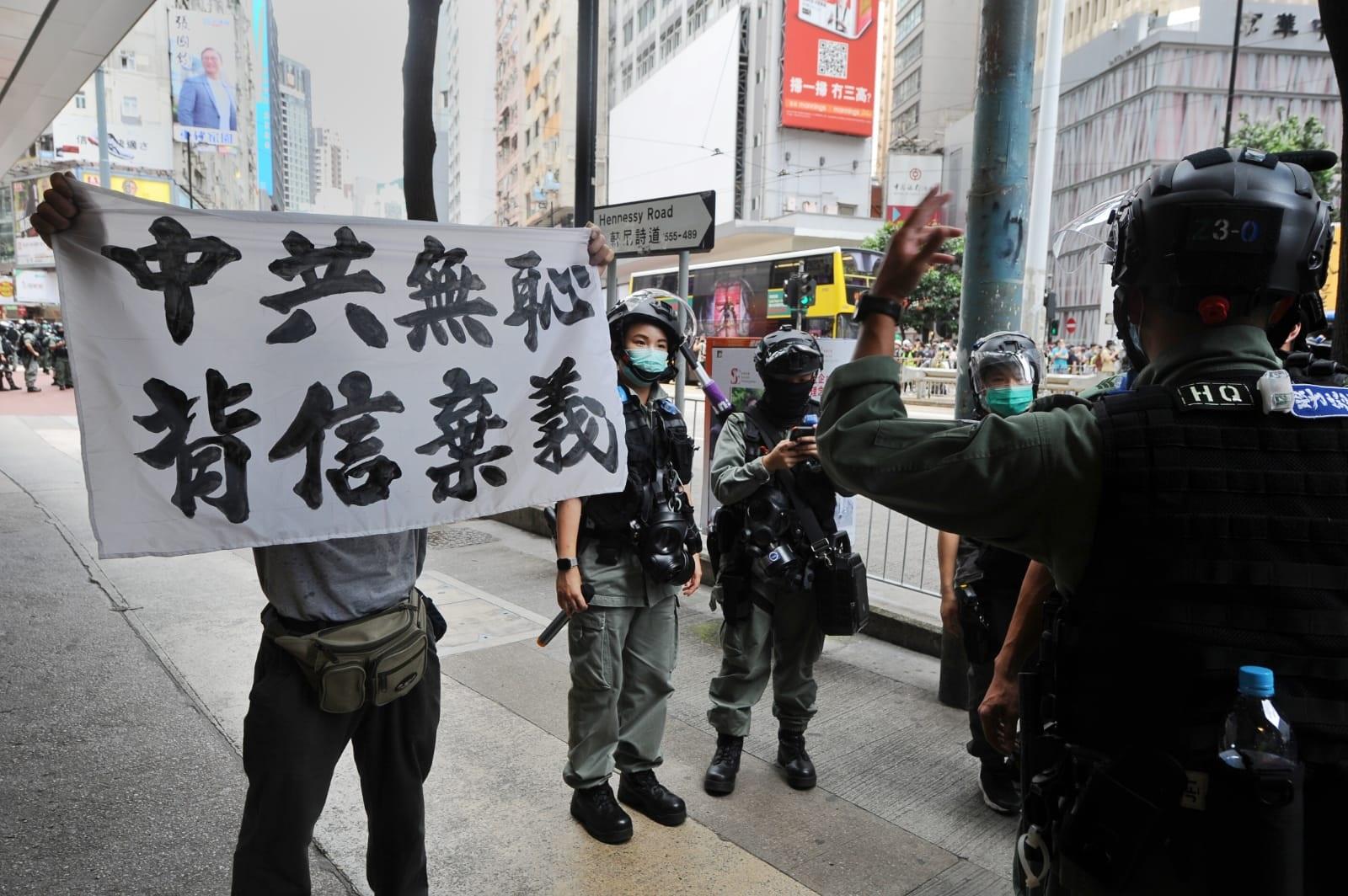 2020年7月1日,香港大量防暴警察衝到SOGO百貨對面驅趕民眾並舉黃旗和藍旗,圖為民眾手持「中共無恥 背信棄義」標語。(宋碧龍/大紀元)