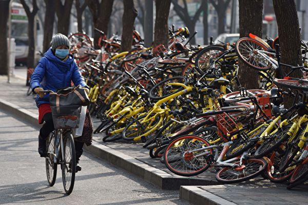 摩拜單車未來將更名為美團單車,摩拜app也將逐步停用。圖為北京街頭的一堆被廢棄的共享單車。(GREG BAKER/AFP/Getty Images)