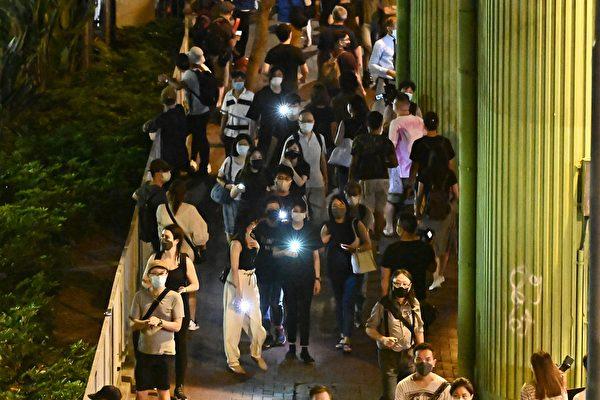 香港當局禁止民眾舉行六四紀念活動,但港人仍以各種形式紀念。圖為維園外圍不少市民舉起點亮的手機步行。(香港大紀元)