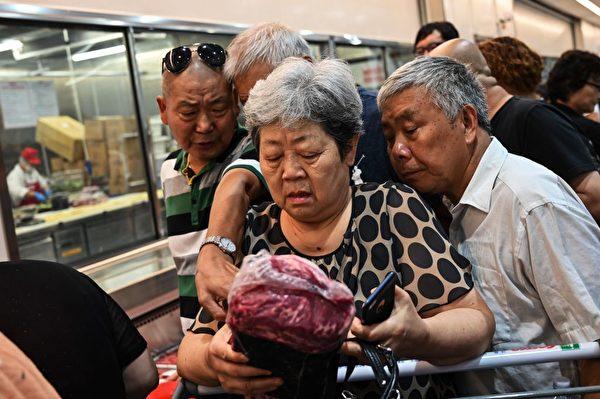 在中美貿易戰激化、官方喉舌不斷高調反美蠱惑下,美資商品依然受到青睞,有學者表示,中國人其實從來不反美。圖為在Costco(好市多)上海門店搶到肉的大媽。 (HECTOR RETAMAL/AFP/Getty Images)