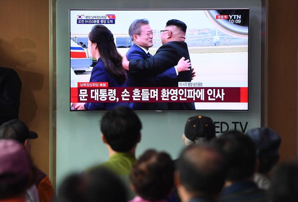 圖為2018年9月18日南韓民眾在首爾火車站觀看電視報道,當日南韓總統文在寅在平壤機場與北韓領導人金正恩擁抱。(JUNG YEON-JE/AFP/Getty Images)