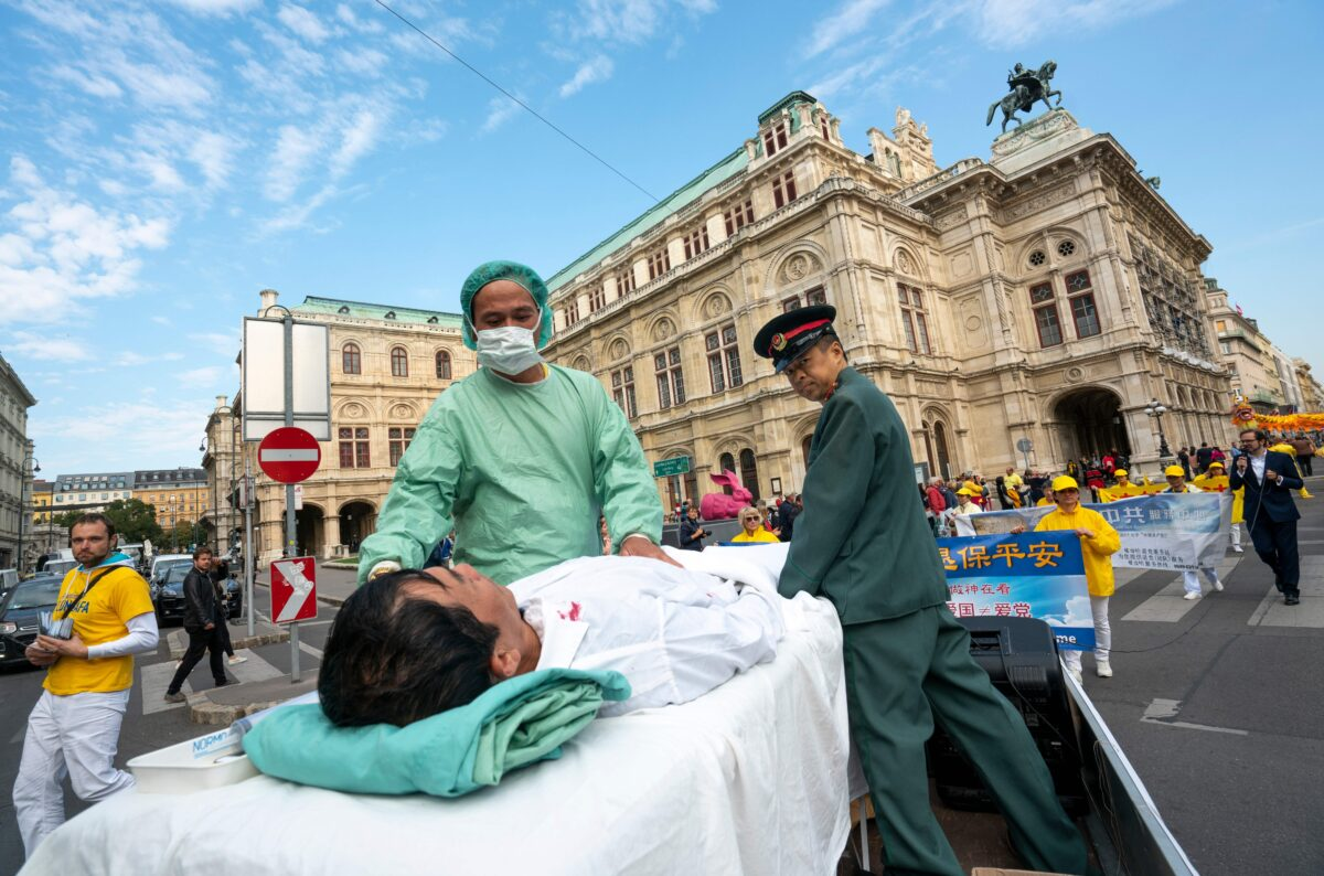 2018 年10月1日,奧地利維也納的法輪功學員在抗議從中共進口人體器官到奧地利的抗議活動中,演示中共對被監禁的學員進行活摘器官。(JOE KLAMAR/AFP via Getty Images)