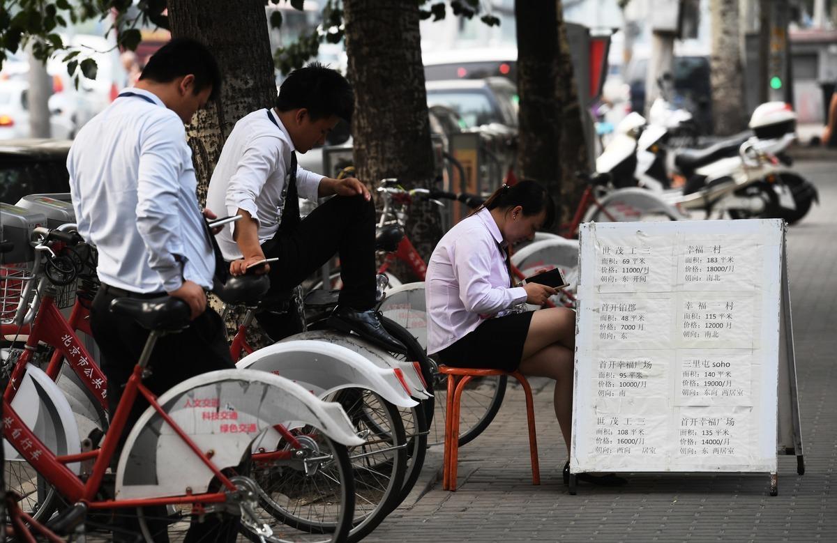 受中共病毒衝擊,大陸樓市低迷,開發商以價換量或成常態。圖為北京街頭的地產經紀。(GREG BAKER/AFP/Getty Images)