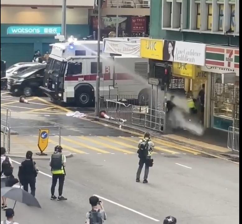 2020年7月1日下午近5時,港警對著一群記者近距離發射水泡,一名記者應聲而倒。(影片截圖)