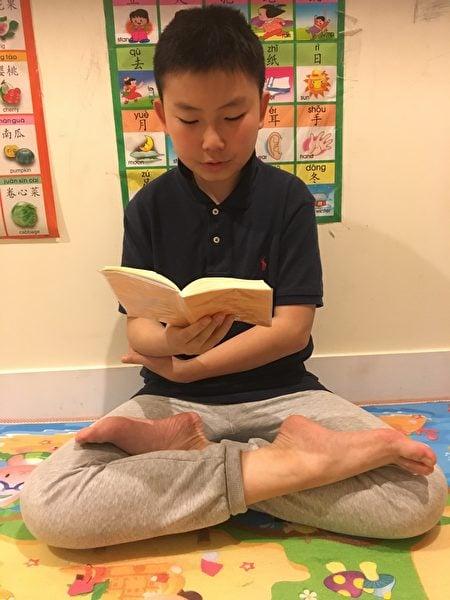 紐約法輪功小弟子王瀚在讀《轉法輪》。(受訪者提供)