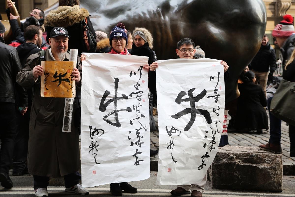 為了表現代表特朗普時代的「牛」字精神,紐約市幾位挺川華人在12月26日相約來到了華爾街。他們手舉標寫著「特朗普時代漢字」的「牛」字書法作品,在銅牛前合照留念。(從左到右為:何哲、劉榮、樓新躍)(施萍/大紀元)